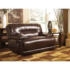 A wide seat, cushioned back and padded arm rests make the Exhilaration power recliner a comfortable place to sit back and  relax. Designed with chocolate leather by Ashley Furniture, this handsome seat is paired with rich contrast stitching.