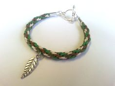 A handmade toggle bracelet made with a kumihimo braid of colours inspired by the forest/nature (green, olive, brown and cream), with a choice of charm.