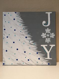 Beautiful 12x12 Christmas painting. Painted on 12x12 canvas with acrylic paints. Pretty feathered out white Christmas tree branches decorated with light blue and dark blue painted Christmas ornaments. Joy painted down the right side with a beautiful white snowflake with blue glitter for the O.
