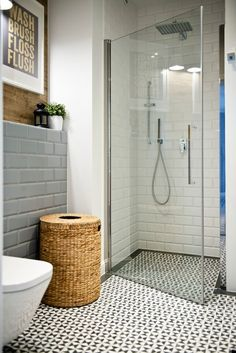 Bathroom with white and grey subway tile and pattern floor tile. Glass shower. Interior decorating. Home decor