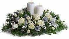 Bellissima composizione con due ceri, rose bianche, pigne, nastri argento e accessori natalizi sui toni bianco argento.