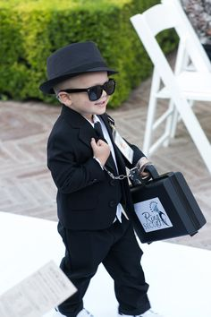"Ring bearer acting as ""ring security"" for the wedding ceremony carrying a briefcase & wearing a suit & sunglasses 