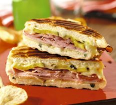 Grilled Cuban Sandwiches 5 tablespoons mayonnaise, divided   1 1/2 tablespoons chopped fresh oregano   2 teaspoons minced garlic   1 (12-oz.) loaf Cuban or French bread (not a thin baguette), halved lengthwise*   3 oz. thinly sliced baby Swiss cheese   6 oz. roast pork, thinly sliced   3 oz. thinly sliced boiled ham   1/3 cup thinly sliced dill pickle