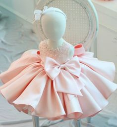 Pink Big Bow Dress--Made To Order - High Quality Round Neckline Sleeveless Knee Length Pearl & Crystal Applique Little Girl Ruffle Dress With Big Bow Front. Perfect dress for baptism, communion, wedding, birthday party or any special occasion. Available from 9 months -12 years. Material: Cotton, satin. Colors: White, Pink & Turquoise. Please do compare your little girl's measurements with our size chart