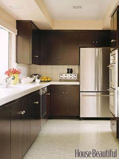 Designer Michael Berman stained the original walnut cabinets in a kitchen the color of black tea to set off the white tile of the countertops.