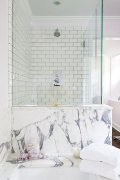 This bathroom design is stunning with the pairing of a dramatic veined marble tub with white subway tiles.