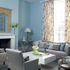 Blue and gray living room with tall floral drapes