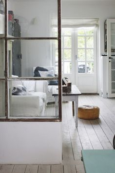 room divider - a half wall with old windows coming out of the phone booth walll...
