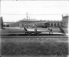 """Railyard Scene at Pullman  Print of photograph showing railyard behind Pullman Factory in Chicago; train car """"Thistle"""" in background, foreground shows 3 men loading rails on rail cart with man in suit sitting on the edge."""
