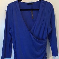 NWT Patty Boutik Ruched Top. Unworn, excellent condition. V neck, faux wrap. Gorgeous shade of blue with 5% spandex. Double layer fabric in the main body of the top. Ruching at sides.  3/4 sleeves. Great with jeans. Patty Boutik Tops