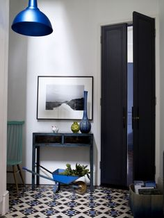 Old and new. Colours from an original Victorian tiled floor are picked out in contemporary accessories - pendant light, glass vases - and contrast with plain, elegant, tall double doors. Quirky touches are added with a vintage console and toy wheelbarrow.