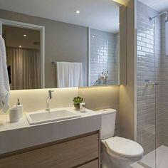 Banheiro com revestimento branco, bancada e vaso sanitário brancos, espelho e paredes creme/bege. Gabinete laminado em madeira natural.
