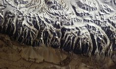 A view of the jagged edge of the Himalayas, the snowy peaks in stark contrast to the deep green of the foothills. | Chris Hadfield