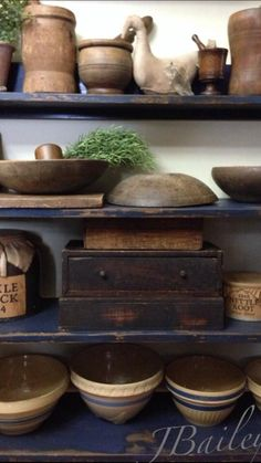 Primitive shelves filled with yelloware bowls, dough bowls, and other primitives.