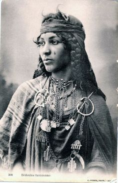 Africa | Tunisian Bedouin in Algeria. Young woman with thick braids, tattoos on her chin and right cheek. Necklaces with pendants in the shape of the ''hand of Fatma''. Sash around her head, fasteners holding her dress to her coat. | ©Jean Geiser, ca. 1905 | Scanned old postcard image.