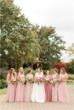 bride poses with bridesmaids in mismatched pink gowns | Planning a romantic fall wedding? Find inspiration here! Conservatory at the Sussex County Fairgrounds Wedding photographed by NJ Wedding photographer Idalia Photography. #IdaliaPhotography #NJWedding #ConservatoryAtTheSussexCountyFairgroundsWedding #RomanticFallWedding
