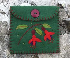 Felt coin purse with hand appliqued and embroidered Fuchsia flowers and leaves. Made in dark green felt with red felt lining, blanket stitched edges and a button fastening. For coins, jewellery or oth
