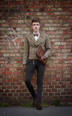 Shop this look for $368:  http://lookastic.com/men/looks/biker-jacket-and-bow-tie-and-dress-shirt-and-zip-pouch-and-gloves-and-chinos-and-derby-shoes/2035  — Tan Leather Biker Jacket  — Brown Bow-tie  — White Dress Shirt  — Brown Leather Zip Pouch  — Brown Leather Gloves  — Black Chinos  — Dark Brown Leather Derby Shoes