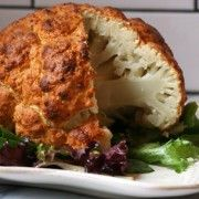 SPICY WHOLE ROASTED CAULIFLOWER  1 tablespoon vegetable oil  1 head cauliflower  1½ cups plain Greek yogurt  1 lime, zested and juiced  2 tablespoons chile powder  1 tablespoon cumin  1 tablespoon garlic powder  1 teaspoon curry powder  2 teaspoons kosher salt  1 teaspoon black pepper