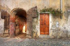 Porte en bois et porte d'entrée au garage en vieille maison de brique dans la ville de Saluzzo, Italie du Nord. Banque d'images