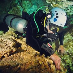 A brave diver squeezes through the cracks while cave diving with his computers. Cave Diving, Scuba Diving, Golf Bags, Brave, Hiking Boots, Computers, Life, Diving, Hiking Shoes