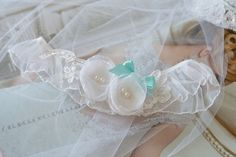 Podwiązka - dwa kwiatki z koronką.  Ręcznie wykonana podwiązka składająca się białej falbanki oraz kwiatków z koronką. Kolor biały, kokardka w kolorze morskim.  Dostępna w butiku Madame Allure! Wedding Garters