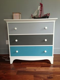 Pretty upcycled chest of drawers, particularly suited to a boy's bedroom in pale grey with highlights of deep red, white and turquoise.