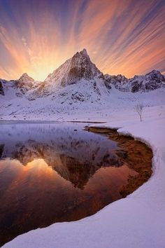 The northern lights and beautiful landscapes in Sweden and Norway - Rays of sunlight streak over a snowy peak reflected in a lake in Lofoten Islands, Norway