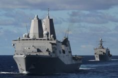 The USS New York leads the USS Fort McHenry across the Atlantic Ocean, Dec. 19, 2014. The ships are part of the USS Iwo Jima Amphibious Ready Group, which carries approximately 2,400 Marines and Sailors of the 24th Marine Expeditionary Unit. The 24th MEU and Iwo Jima ARG deployed last week as a flexible, sea-based force tasked with providing crisis response across the range of military operations, from armed conflict to humanitarian assistance. (U.S. Marine Corps photo by Lance Cpl. Dani…