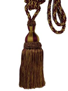 """Trimland Single Tassel Drapery Tieback 3337Cavalier CollectionColor - 7653 Cabernet Brick Red & Gold MixSold by the piece.Content - 100% Cellulose Acetate over 100% CottonTassel measures 10"""".  Top of knot to bottom of tassel measures 13"""".1/2"""" Diameter Cord.  Cord spread 38"""".Made in TurkeySmoke-free environment.Orders are shipped within one business day. Tab Curtains, Chair Ties, Cellulose Acetate, Light Teal, Cavalier, Drapery, Red Gold, Tassel Necklace, 10 Top"""