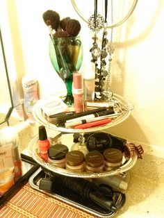 """A 3 tier makeup stand I made all by myself! Total cost was $5. 3 metal serving trays from the Dollar Tree and a hot glue gun. I used 2 mini wine champagne glasses to hold them up and give them a little """"class"""" lol. The bottom tier is for holding my brush and Chi, while the first 2 are for makeup. I'm using a colored wine glass for my makeup brushes."""
