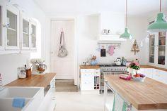 aranżacja białej kuchni z drewnianymi blatami,blaty z naturalnego drewna w białej kuchni,skandynawska kuchnia z turkusowymi lampami,emaliowa...