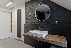 salle de bain noir et bois avec plan vasque en bois, parement mural en brique noire et miroir suspendu