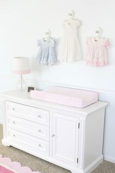 """Vintage"" Baby Dresses hanging above changing table"