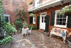 """""""The brick courtyard is filled with dappled light and has great structure; a second story balustrade adds interest to the double height space. Contrasting trim on doors and windows provides added detail; the courtyard doesn't require a lot of added detail."""""""