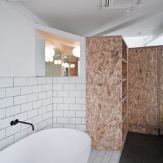 The Cubby House by Edwards Moore OSB used in bathroom alongside white oversized brick pattern tiling Image from Dezeen Chipboard Interior, Osb Board, Melbourne, Oriented Strand Board, Cubby Houses, Concrete Floors, Cubbies, Bathroom Furniture, Pallet Furniture