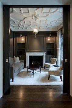 living rooms - black pocket doors white geometric pattern overlay ceiling taupe built-in cabinets stone fireplace gray linen sofa pair tufted chairs