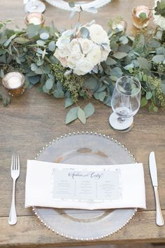 white and blush pink florals with eucalyptus leaves, long wooden tables with…