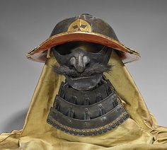 "Antique Japanese samurai helmet (kabuto) and mask (menpo): lacquered with gold leaf inset gingko and triangle mon, the helmets rims flared up; the menpo with full mustache and four tiered throat guard (yodare-kake), Edo Period (old repairs, heavy wear and use); L: 13"" (helmet) lucite stand; Provenance: by repute helmet worn by a samurai of the Tachibana Clan, authenticity from The Nishiki Gallery"