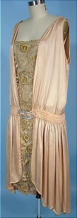 "c. 1927 Flapper Dress of Blush Pink/Peach Silk and Lace--This dress is a blush peachy-pink silk charmeuse, ruched at the low waistline with rhinestone ""buckle"" at front.  The elliptical hemline is fab, lower in the back than front.  And then comes that terrific front panel of embroidered gold and nude net lace which also wraps around to hint through at the underarms and at ""v"" back."