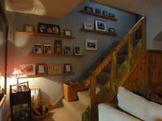 "Rosemary Prock (Sow's Ear Studio, Schenectady New York) turned a dark stairway into a fanciful piece of art.  She coordinated her ""Russian Dacha"" stairway creation with narrow shelves allowing quick rotation of photos along the wall.  We're Thrilled!"