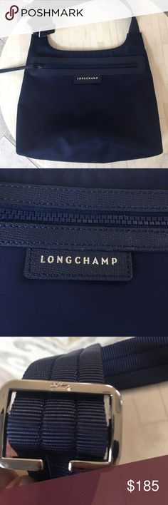 "Longchamp Navy Crossbody Bag 10 ½""W x 9""H x 3""D. (Interior capacity: small.) 15"" - 27 ½"" crossbody strap drop. A slim, stylishly smart bag goes the distance with durable, water-resistant nylon construction and rich leather trim. Lightweight, comfortable and attractive, it folds flat when not in use, making it a perfect travel companion. Top zip closure. Adjustable crossbody strap. Interior zip pocket. Nylon with leather trim. Like new condition. Longchamp Bags Crossbody Bags"