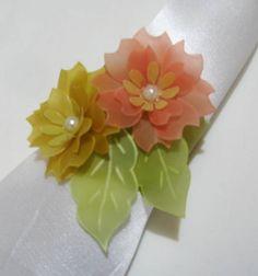 Porta-guardanapo em papel vegetal tingido, com aplicação de 2 flores com centro em pérola ou cristal. Pedido mínimo: 15 unidades. R$ 6,50