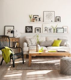 44-Living room with sofa, narrow shelves with black and white pictures and photos, desk and rattan armchair 00433241