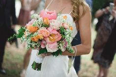 Vibrant summer colors fill this arrangement of orange roses and fuchsia peonies accented with baby's breath