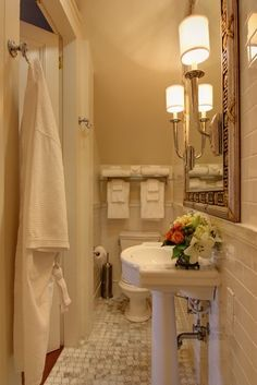 This narrow bath, a converted storage closet, proves that high style sometimes comes in small packages. The designers tucked the toilet and shower at opposite ends and kept the fixtures shallow. Graceful sconces and subway tile walls draw the eye upward; a mirror with a Greek key pattern on the frame expands the room visually.