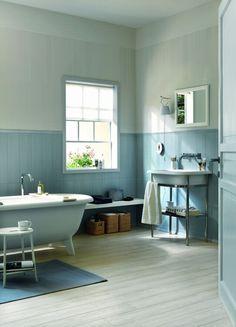 murs en blanc et bleu clair et un petit tapis de bains bleu