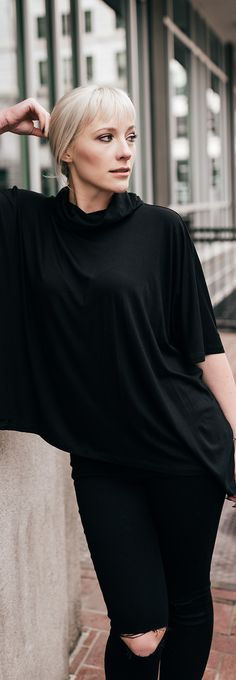 Black cape top with ripped jeans...so comfy and so flattering! Uber chic.