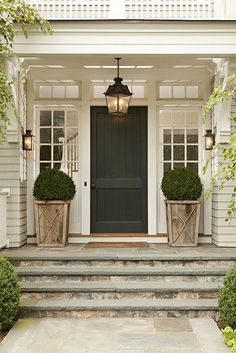 Front porch with outdoor wall lights and lantern pendant and topiary bushes on either side of door