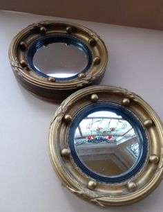 PLEASE NOTE THERE ARE A PAIR AVAILABLE - BUT EACH MIRROR IS LISTED INDIVIDUALLY AND PRICED AT £95 FOR A SINGLE MIRROR.  These are really sweet little mirrors - they take inspiration from much larger ones which are often hung on a wall. These ones are though much rarer, being of a miniature size. They are made of wood which has been gilded. The mirror is circular (and flat, not with any curve) and is nice and clear with no spotting or issues. The mirror is surrounded by a fine black reeded…
